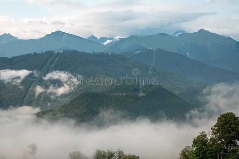 Clouds and fog on the slopes of mountain ranges with snowy peaks in summer stock photo