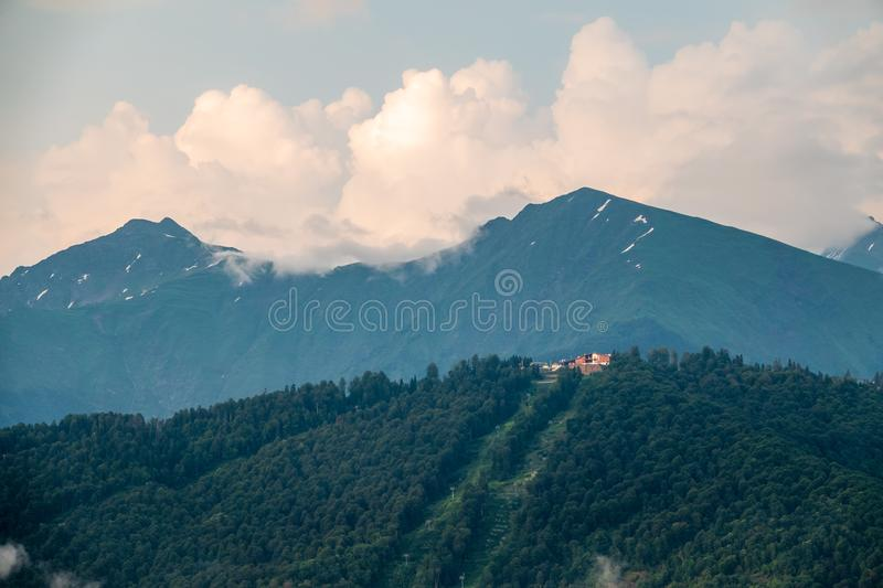Clouds and fog on the slopes of mountain ranges with snowy peaks in summer stock images