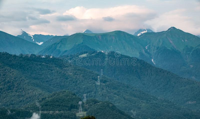 Clouds and fog on the slopes of mountain ranges with snowy peaks in summer stock photography