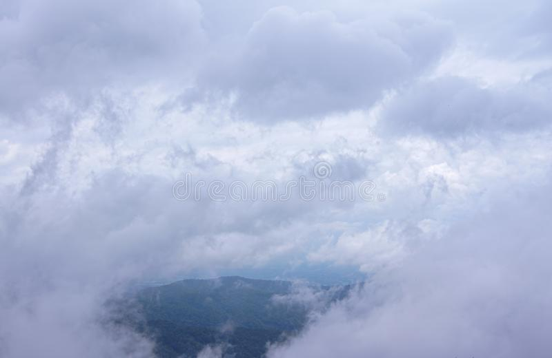 Clouds and fog are soft fluffy scattered all over, passing through gaps, seeing as green mountains stock photos