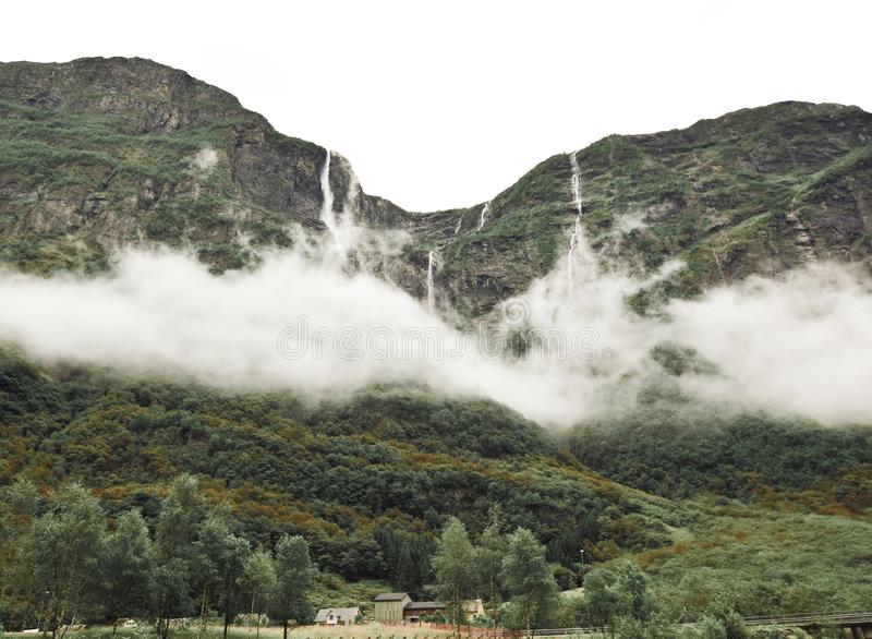 Clouds form moody cloaks around the high waterfalls of Norwegian fjords. Clouds form moody cloaks around the high waterfalls of Norway in the fjords royalty free stock image