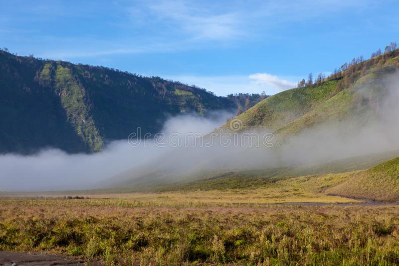 Clouds in green valley of Tengger caldera near. Clouds in green valley of Tengger caldera near Bromo volcano at Java island in Indonesia stock photos