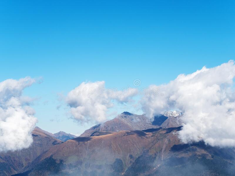 Clouds lowered on mountain peaks on a clear sunny day stock photography