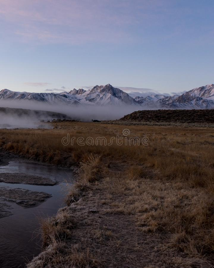 The clouds of mist form half way up the mountain during an early morning sunrise royalty free stock image