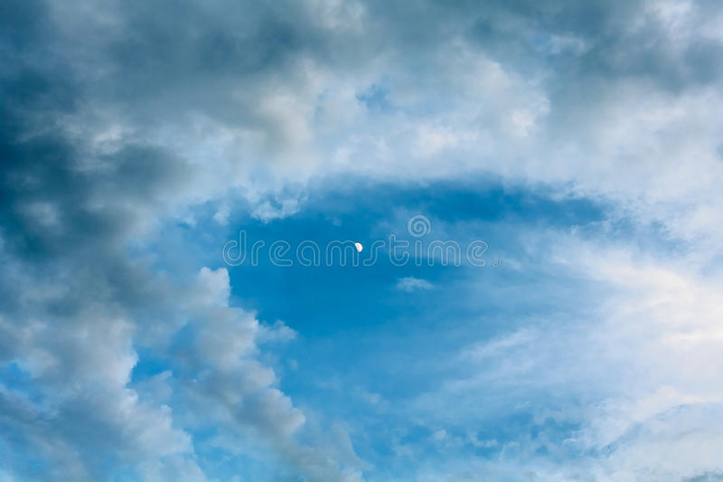 Clouds and the moon on a blue sky. Picturesque clouds and the moon on a blue evening sky stock image