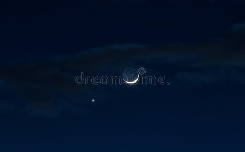 The Clouds and the Moon. Crescent moon with Jupiter and Saturn in the night sky with the evening clouds in Utah USA royalty free stock image