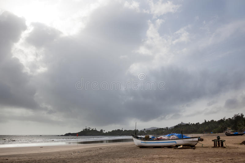 Clouds over the beach. Fishing boats on the sand at the beach Patern in Goa royalty free stock images