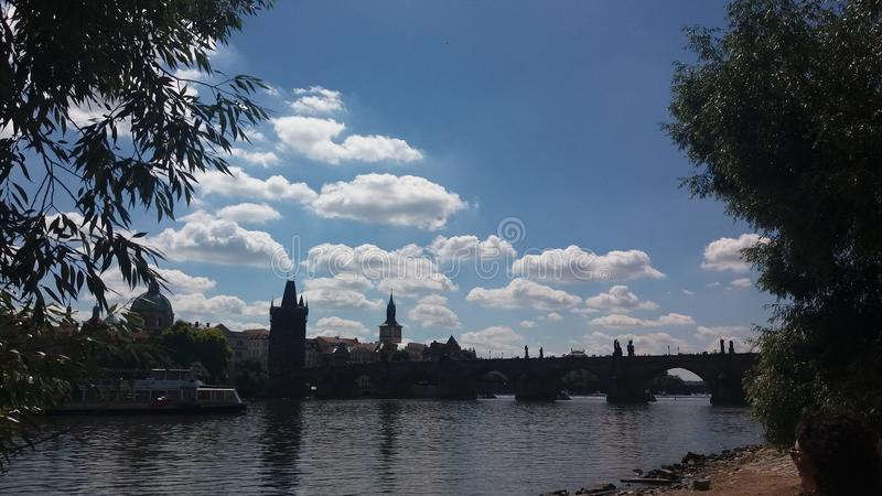Clouds over charles bridge in prague stock photography