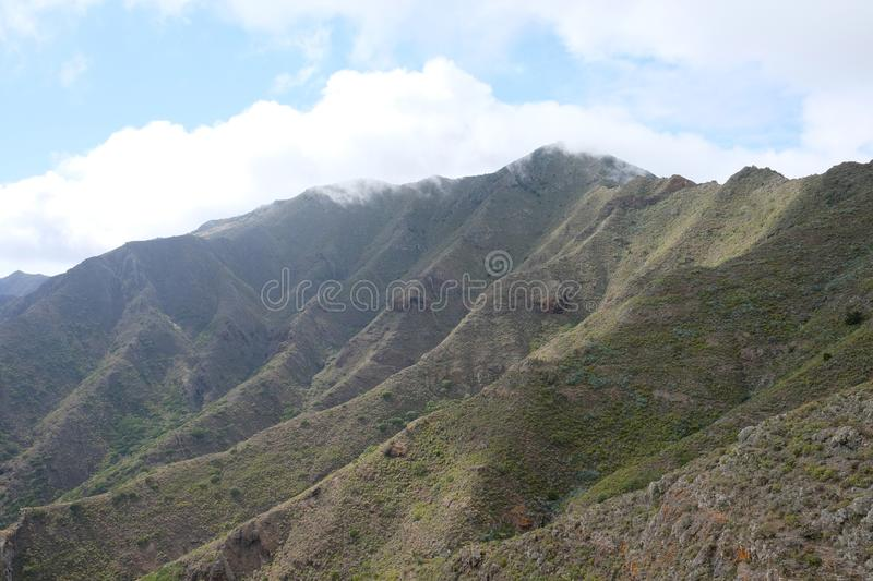 Clouds over green volcanic mountain cliffs stock photography