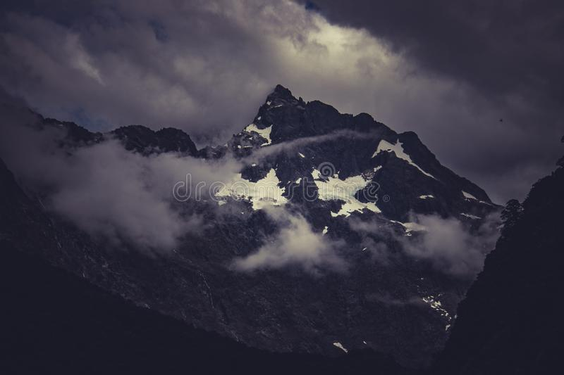 Clouds over mountain peak. Thick clouds floating near snowy peak of mountain on south Island of New Zealand stock image