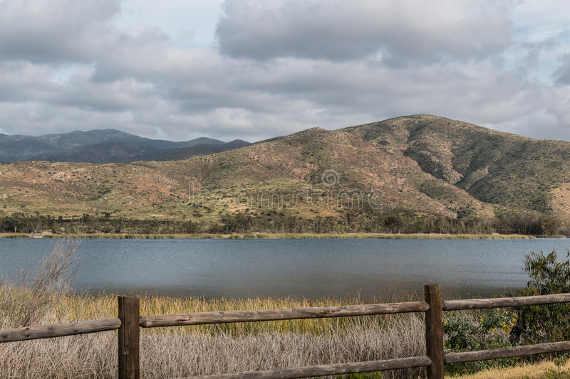 Clouds over a Mountain Range and Lake in Chula Vista, California. Clouds covering a mountain range with a lake and fence in the foreground at Otay Lakes County stock photos