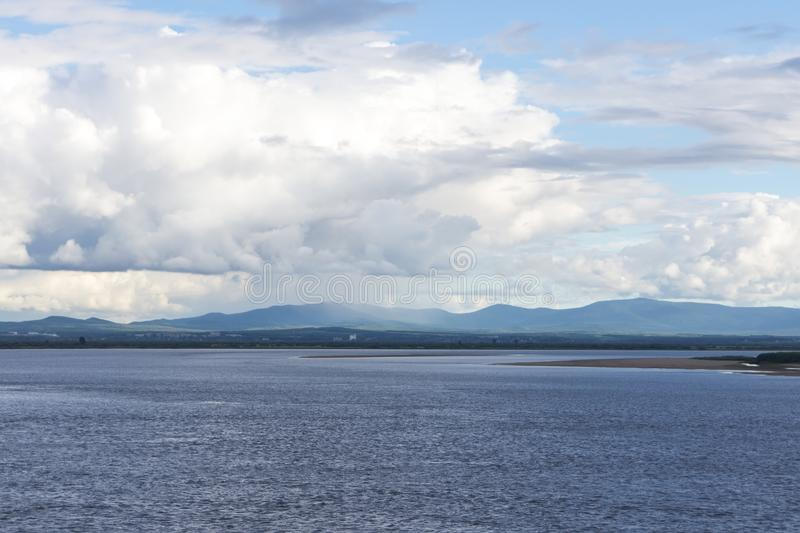 Clouds over the mountains and the river. Clouds over the mountains Khekhtsir and the Amur river stock photography