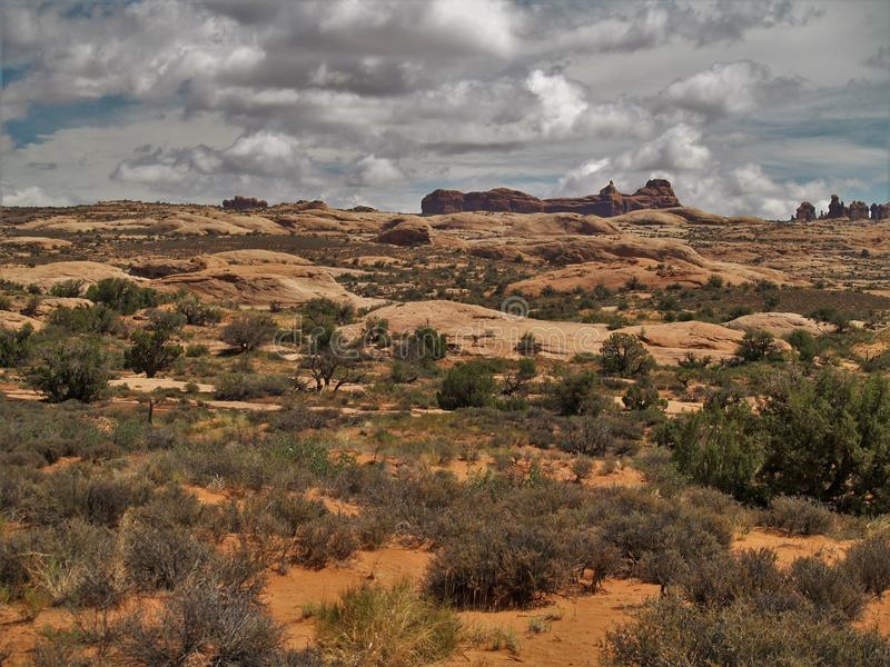 Clouds over Rock Formations at Arches National Park. Arches National Park near Moab, Utah is red rock country. It has over 2000 natural stone arches and numerous stock image