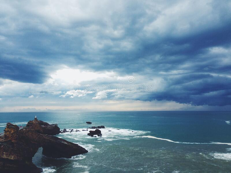 Clouds over rocky coast stock images