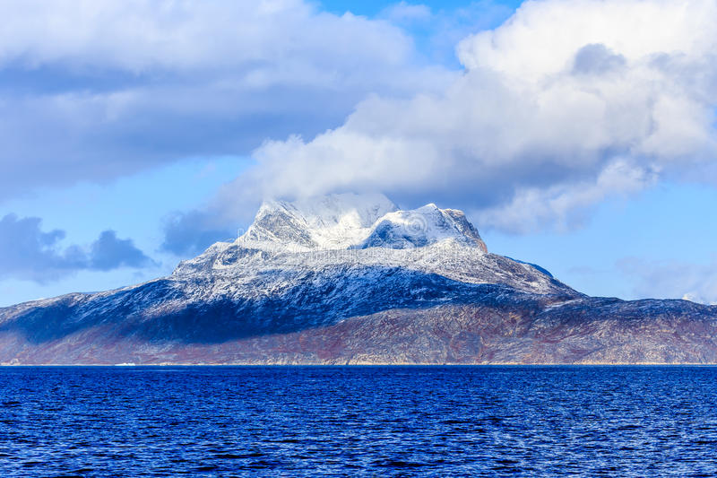 Clouds over Sermitsiaq mountain covered in snow with blue sea in stock photo