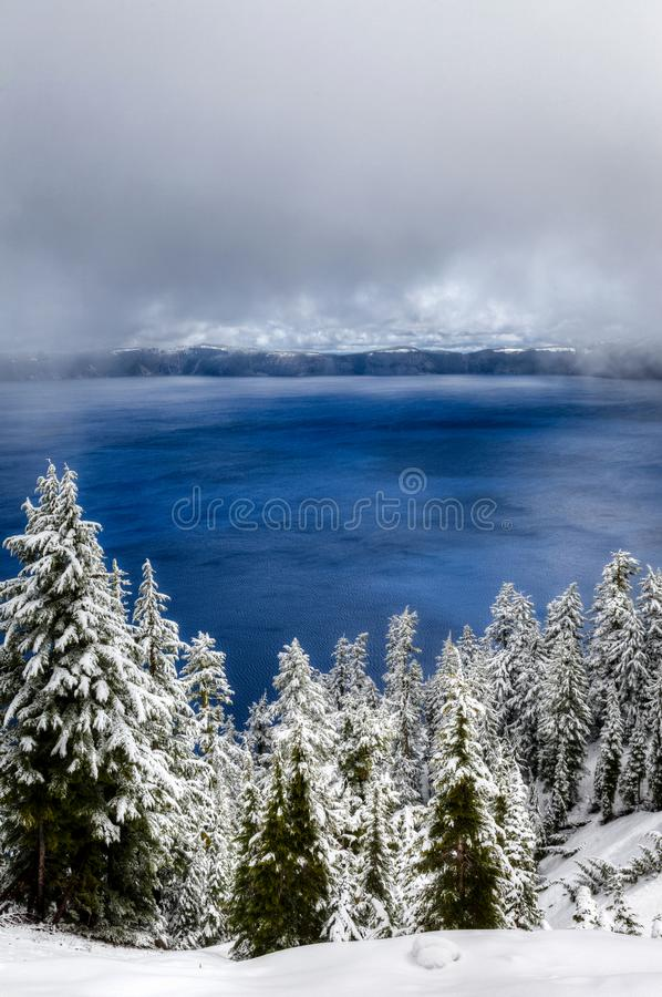 The clouds part for a peek at the deep blue water of Crater Lake with some trees in the foreground royalty free stock photo