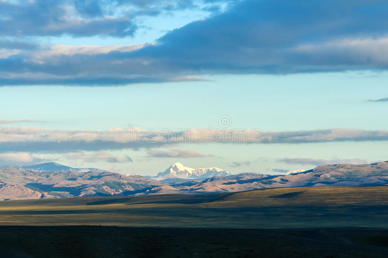 Clouds passing over mountain pinnackle in sunset light stock photos