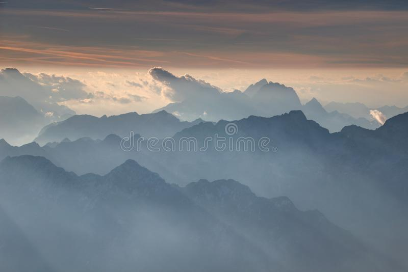Clouds and peaks rise above jagged blue ridges in Julian Alps. Clouds, Jof di Montasio and Fuart peaks rise above serrated blue ridges under shining horizon in stock images