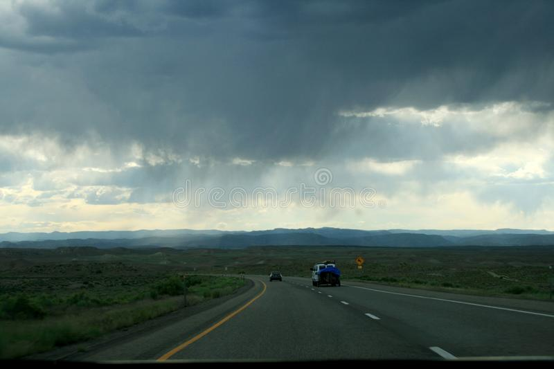 Clouds and rain over a highway in the state of utah, USA. The highway passes through the green plain. Rain ahead stock photography
