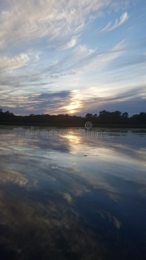 Lake reflections. Clouds reflect off the river like a mirror royalty free stock photography