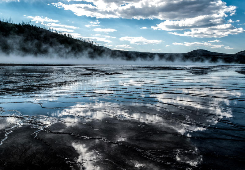 Clouds Reflected in Grand Prismatic Spring - Yellowstone National Park. Blue sky clouds reflected in the mineral terraces of grand prismatic hot spring in stock photography