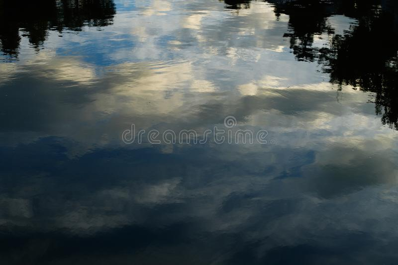 Clouds reflected in the water. An ancient stately home in the historic city center of Jianshui. Yunnan, China. November, 2018 stock photo
