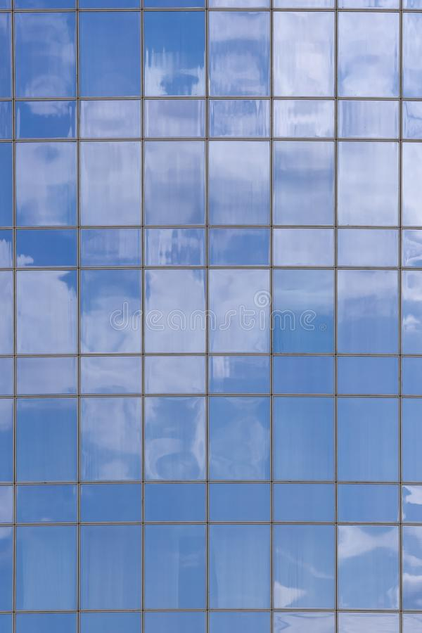 Clouds reflected in windows of modern office building. Glass, sky, business, architecture, city, blue, wall, urban, steel, corporate, background, structure stock photo