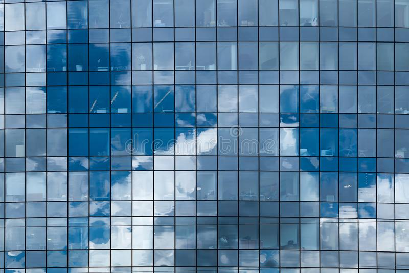 Clouds reflected in windows of modern office building. Glass, sky, business, architecture, city, blue, wall, urban, steel, corporate, background, structure royalty free stock photos