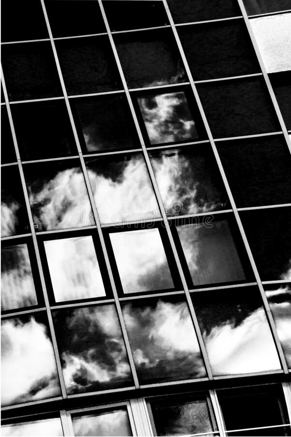 Clouds reflected in windows of modern office building. Skyscraper in the city . Black and white concept.  royalty free stock photography