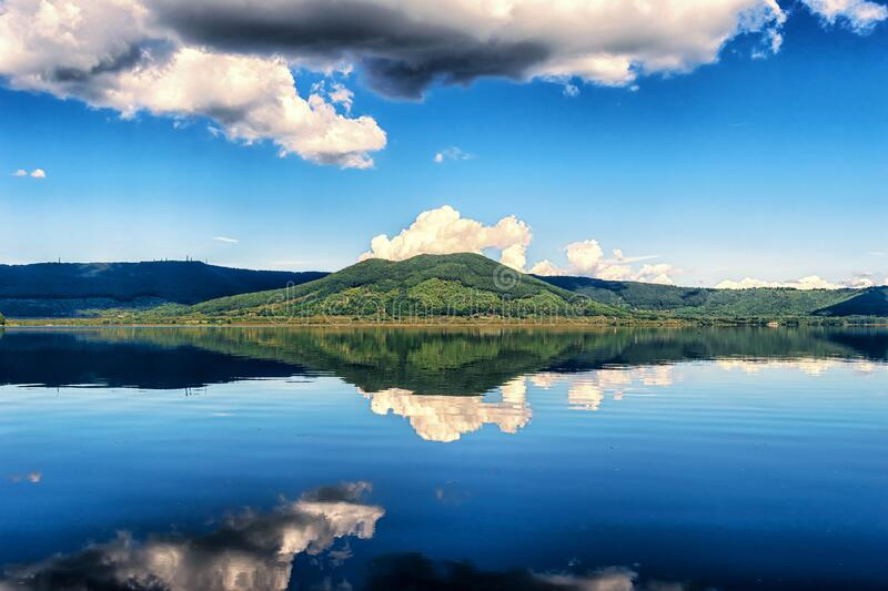 Clouds reflecting on blue lake stock photos