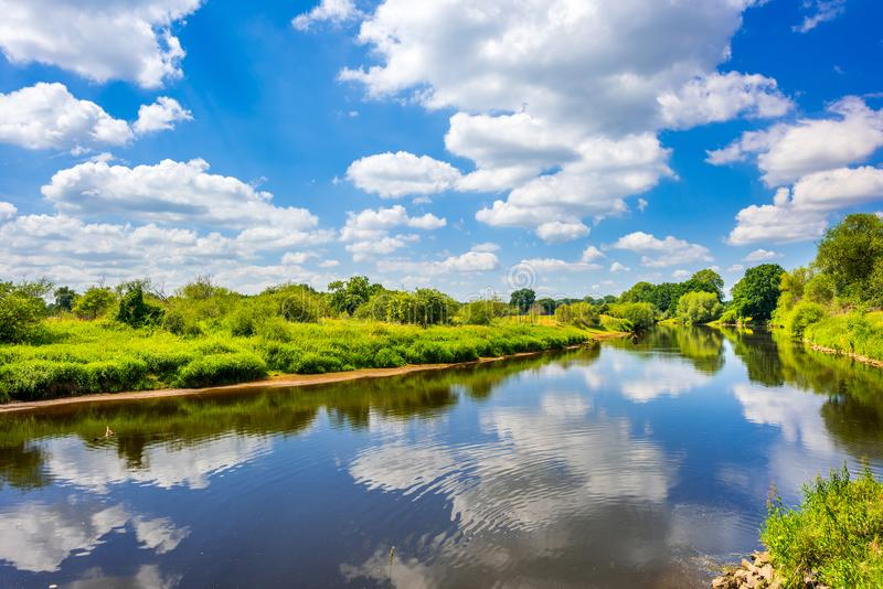 Clouds reflecting in Ems River, Emsland, Germany. Clouds reflecting in blue waters of Ems River in rural Emsland region, Germany on sunny summer day royalty free stock images
