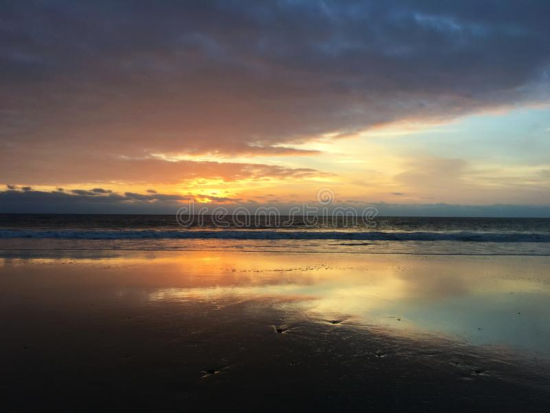 Sunset Walk on the Beach in Ecuador. The clouds and remaining daylight reflect on the water as the sun sets over the Pacific ocean as waves gently roll onto the stock image