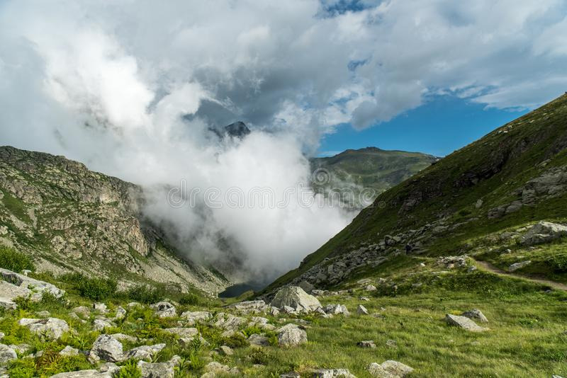 Clouds are rising above tarn near touristic path in mountains. royalty free stock photo