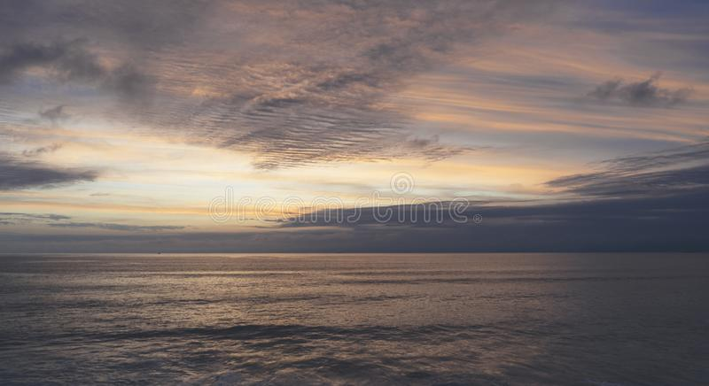 Clouds sky and sunlight gold sunset on horizon ocean. Background seascape dramatic atmosphere rays sunrise. Relax view waves water. Sea, mock up nature evening royalty free stock photo