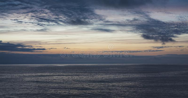 Clouds sky and sunlight sunset on horizon ocean. Silhouette person on background seascape dramatic atmosphere rays sunrise. Relax. View waves water sea, mockup royalty free stock image