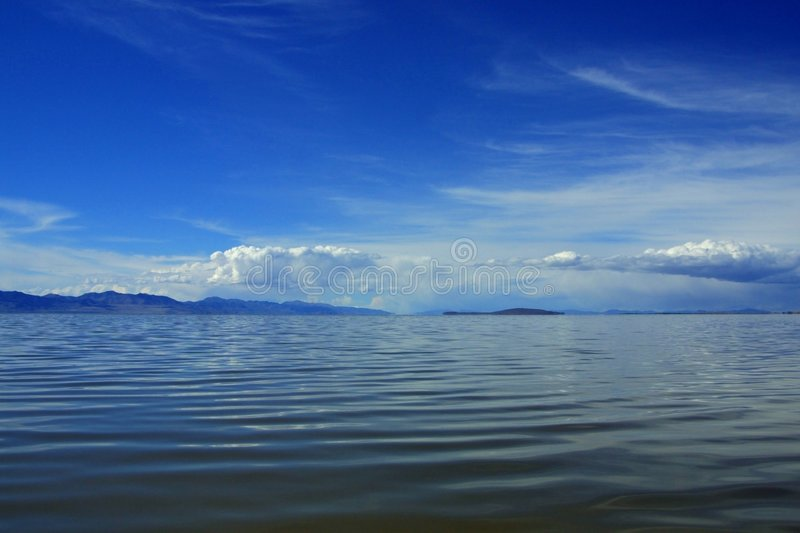 Clouds, sky, water, and mountains royalty free stock photo
