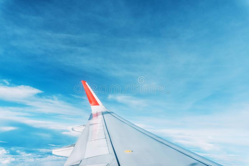 Clouds, sky and wing aeroplane as seen through window of an aircraft stock image