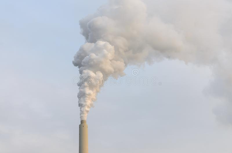 Clouds of smoke belching from industrial chimney stock photos