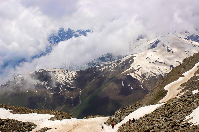 Clouds and snow clad mountains becoming one and trekkers at the base. Himachal Pradesh stock photo
