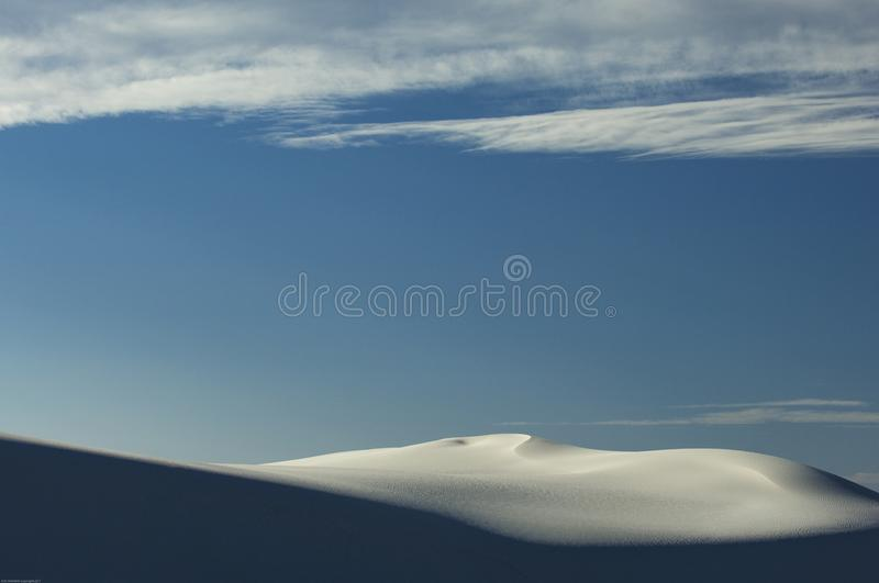 Clouds hang above the hite dunes of White Sands National Monument, New Mexico. Clouds and solitude surround the dunes of White Sands National Monument, New stock photo