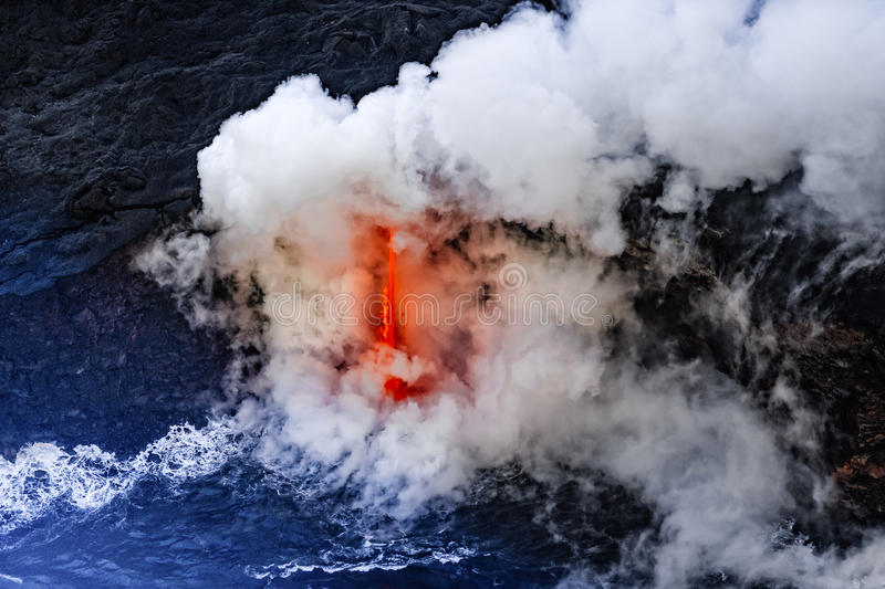 Clouds of steam and rocks fly through the air as Kīlauea erupts and lava clashes with the cold water royalty free stock photos