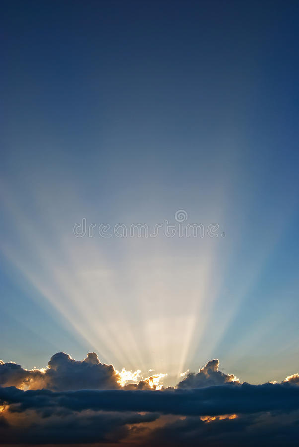 Clouds and sun beams. Sun beams from a dark cloud royalty free stock images