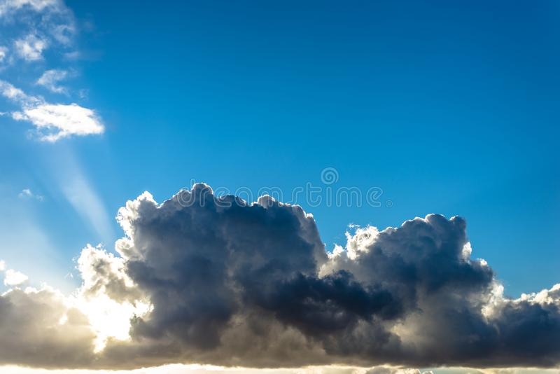 Clouds and sun in a blue sky at sunset stock photos