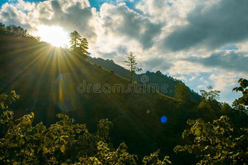 Clouds among the sun and lonely house on the hill stock photography