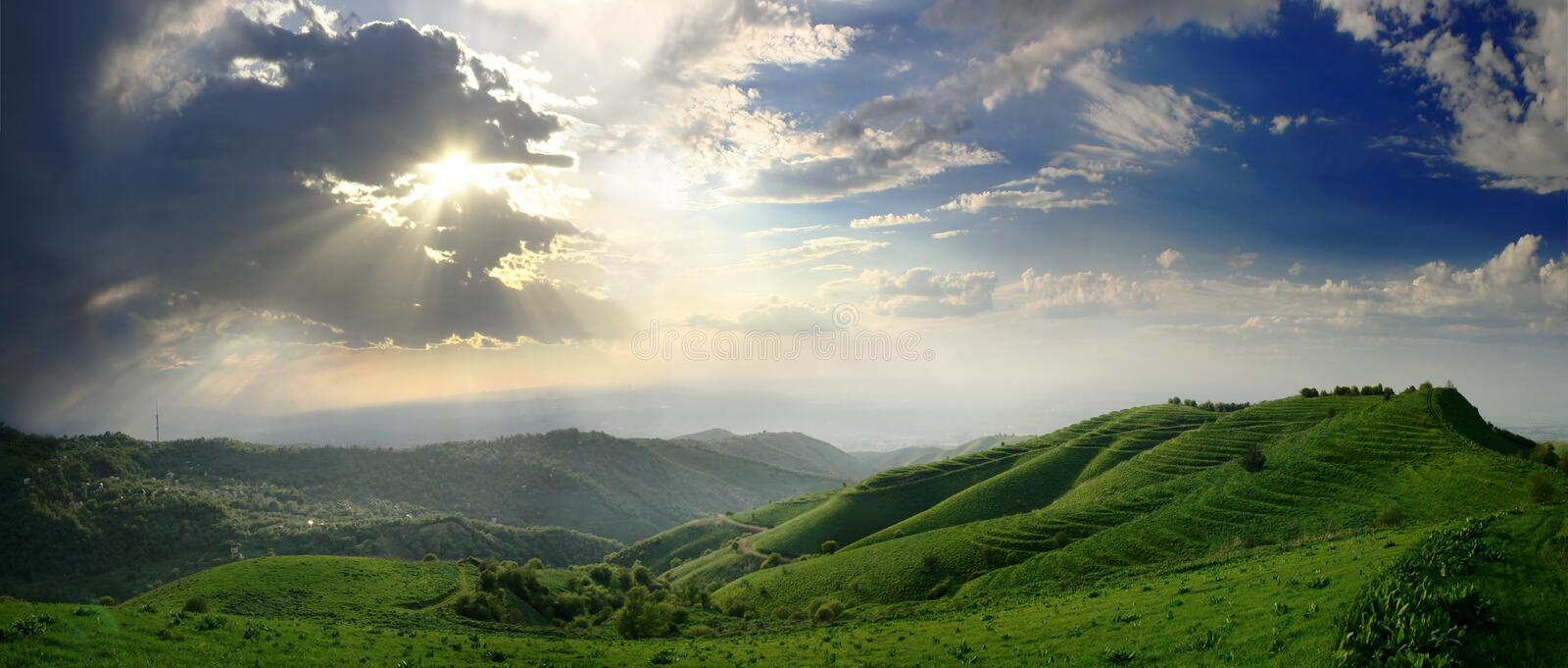 Clouds, sunbeam and hills stock photos