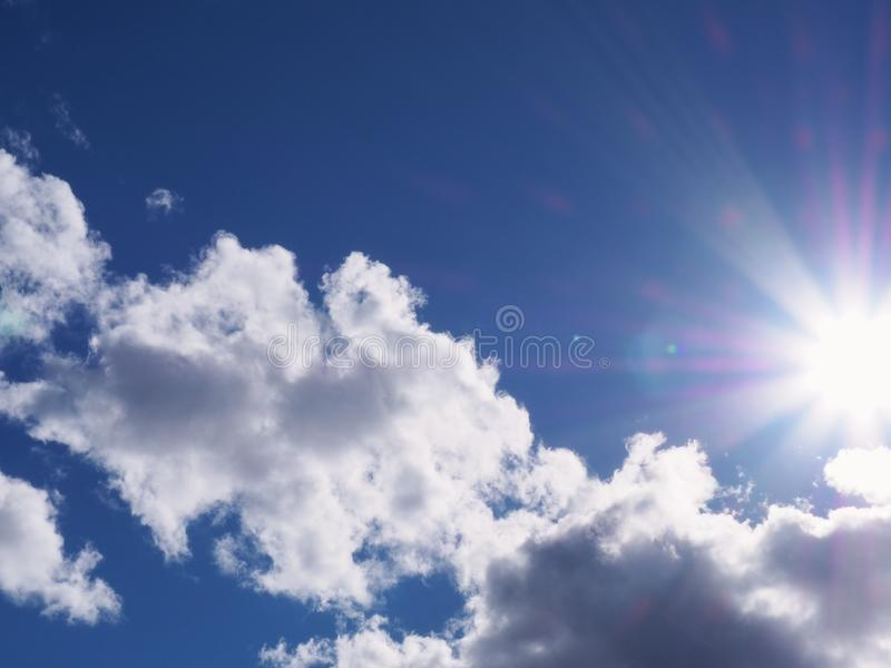 Clouds with Sunburst. Fluffy clouds and a bright sunburst in the summer sky stock photography