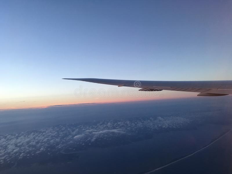 Clouds Under the Wing. The imminent Sunset is visible with clouds under the wing of a plane in flight royalty free stock photos
