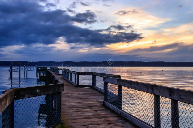 Blue and yellow sunset over wooden dock. Clouds and weather over a wooden dock with sunset stock photos