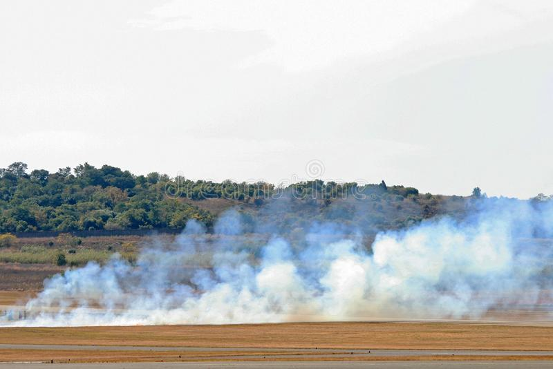 CLOUDS OF WHITE SMOKE DURING PYROTECHNIC DISPLAY. View of white smoke on an airfield during pyrotechnic display as part of mock mini warfare royalty free stock photo