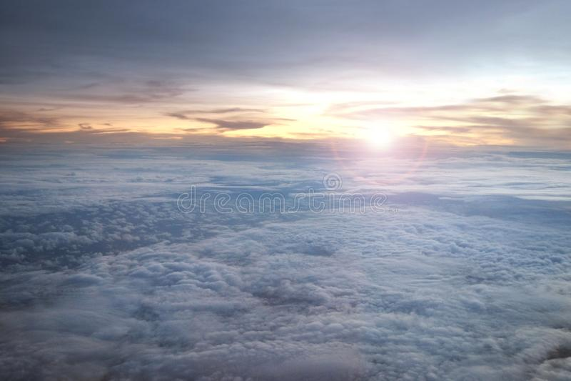 Cloudscape acima do céu com o nascer do sol no horizonte da janela de um avião fotografia de stock